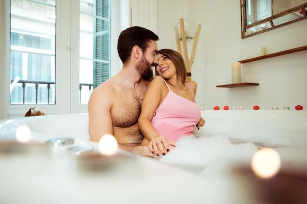 물과 거품 스파 욕조에서 웃는 여자를 포옹하는 사람