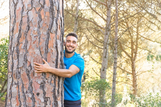 Man hugging tree in lovely forest