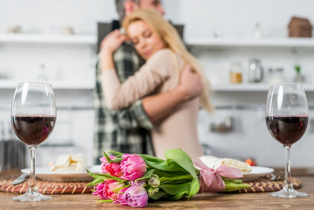 Man hugging with woman near table with flowers and glasses of wine