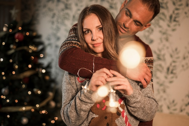 Man hugging woman from back in sweaters near christmas tree