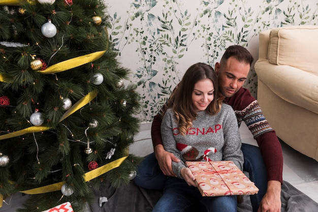 Man hugging woman from back with gift near christmas tree