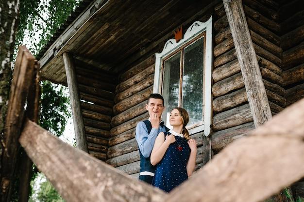 古い木造のスタイリッシュな家の近くに立って後ろから男ハグ女性