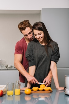 Man hugging woman from behind and cutting orange