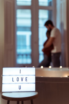 Man hugging woman near spa tub and i love u title on lamp