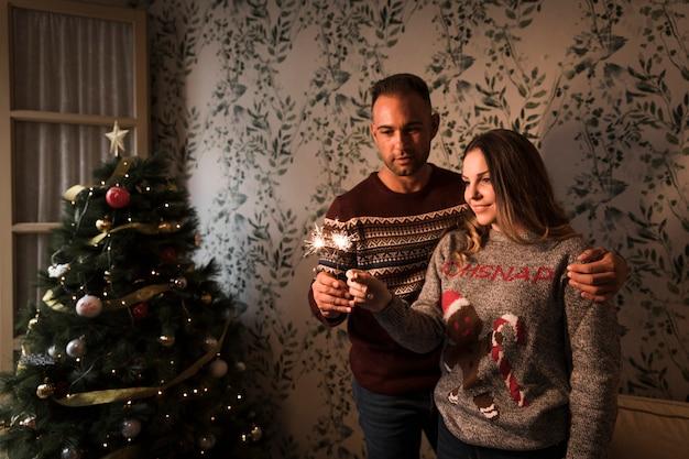 Man hugging woman with bengal lights near christmas tree