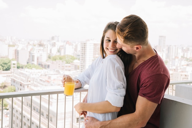 Man hugging woman with glass of juice on balcony