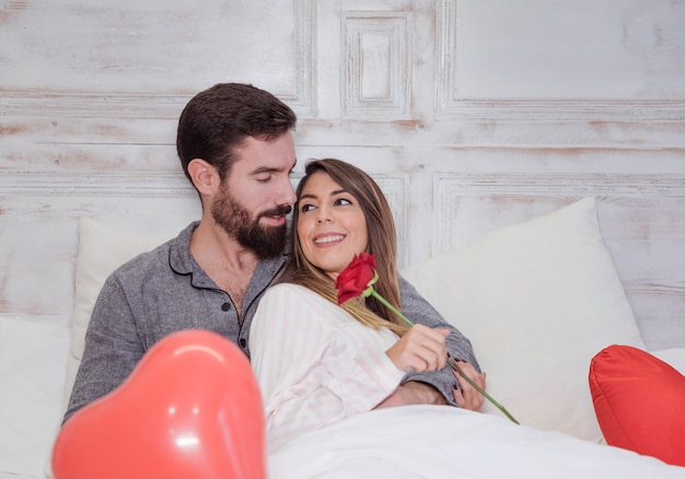 Man hugging woman with rose on bed