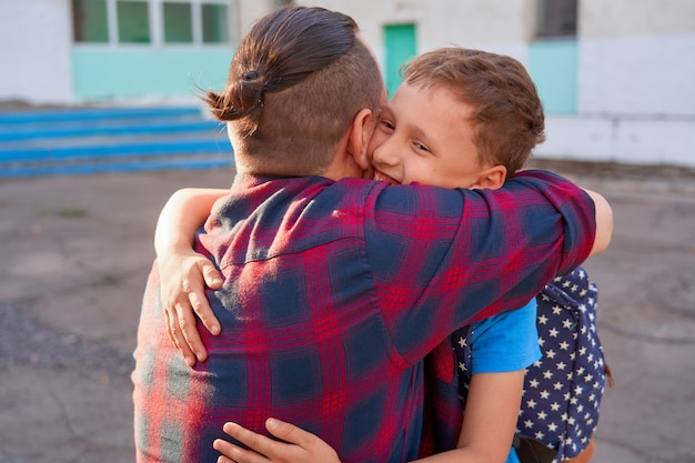 Мужчина обнимает своего ребенка перед школой