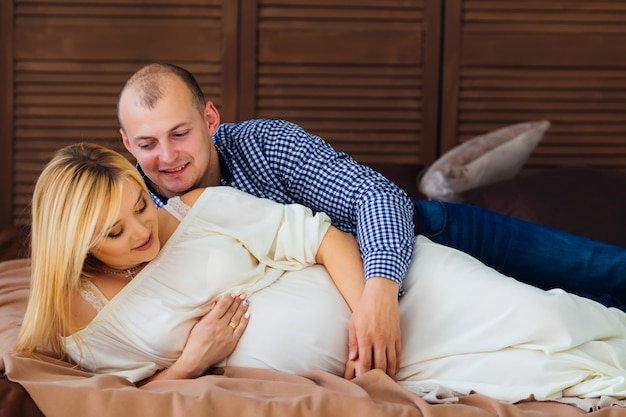 A man hugs his pregnant wife with her belly on her bed