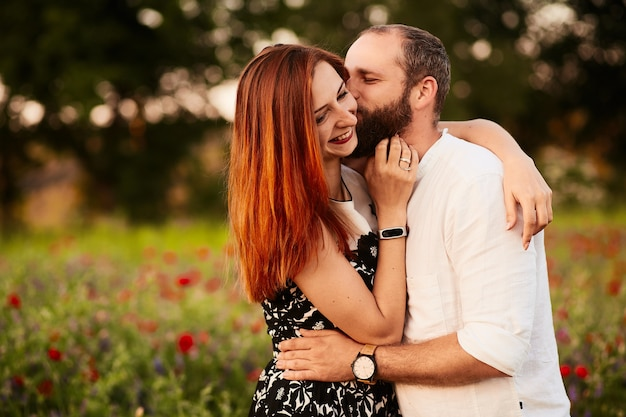 Man hugs his woman tender standing on the field full of poppies