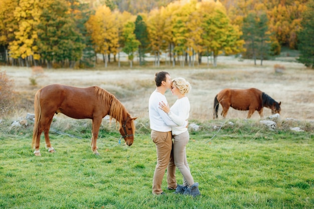 Man hugs and kisses woman on the forehead against grazing horses in the autumn
