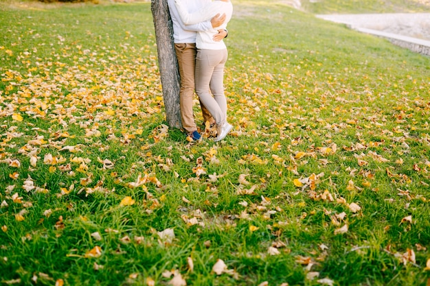 Man hugs woman in beige pants on a scene of greenery in the autumn forest closeup