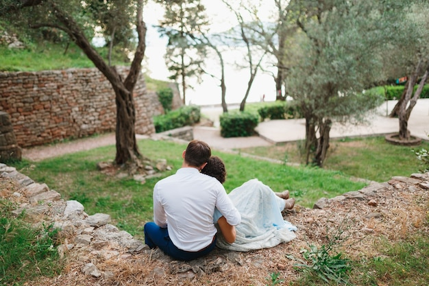 Man hugs woman by the shoulders while sitting on a stone fence between green trees in an olive grove