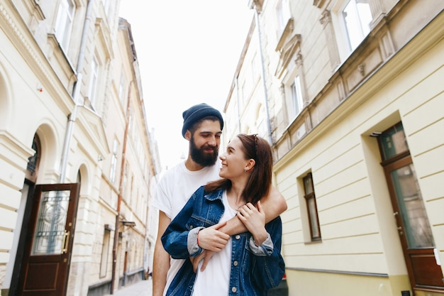L'uomo abbraccia la donna da dietro in piedi con lei per la strada