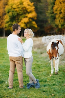Man hugs a woman while standing on the lawn in the autumn forest horse grazing on the lawn