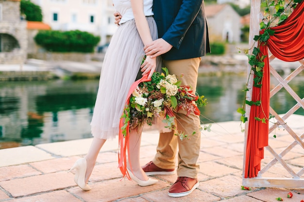 Man hugs woman with a bouquet of flowers in her hands while standing on the pier near a decorative