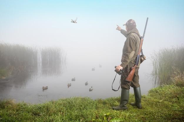 총과 쌍안경을 가진 남자 사냥꾼입니다. 사냥 기간 개념입니다.