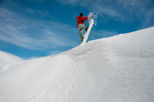 Man i is jumping on a blue snowboard from a snowy mountain