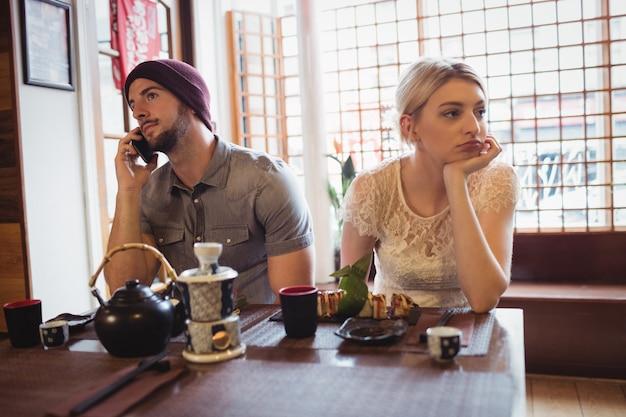 Мужчина игнорирует женщину во время разговора по телефону