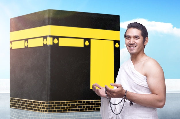 Man in ihram clothes standing and praying with prayer beads with kaaba and blue sky background