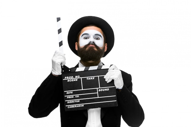 Man in the image mime with movie board