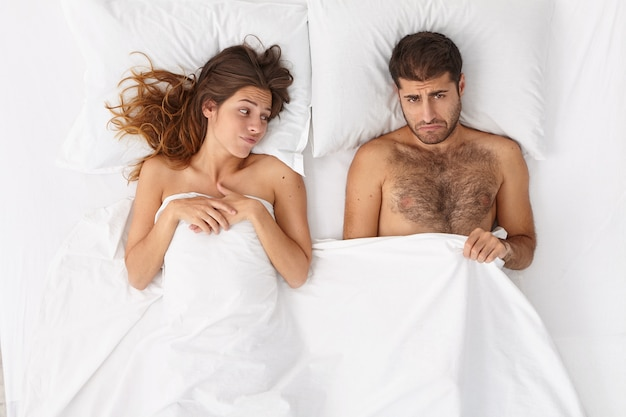 Man impotent has erectile dysfunction, looks under blanket with frustrated expression, unsatisfied woman lies near, have relationship problem because of sex failure. mens health and impotence concept