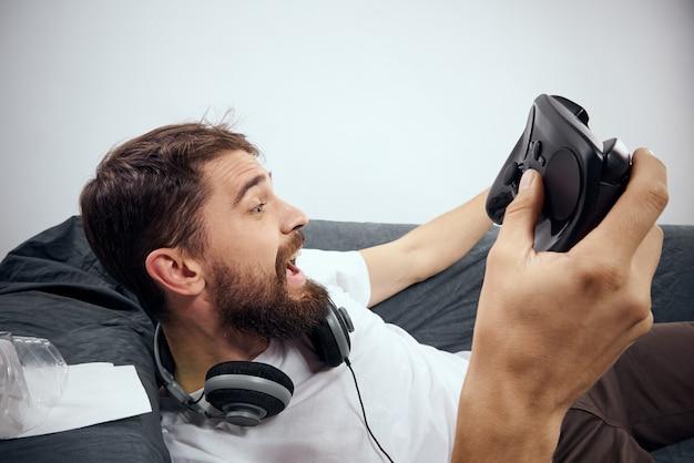 3 dメガネの男は、自宅のソファーにヘッドフォンでジョイスティックを使ってコンソールでコンピューターゲームをプレイします。