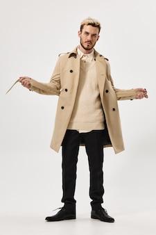 Мужик в бежевом пальто модная прическа для осеннего стиля студии в полный рост