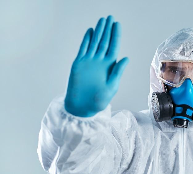 Человек в костюме биологической опасности делает знак остановки