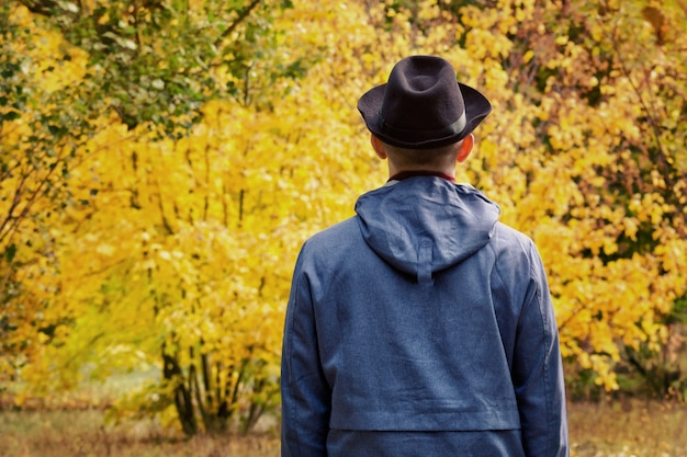 검은 모자에있는 남자는 숲에 서있다