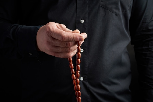 Мужчина в черной рубашке держит в левой руке коричневые каменные четки