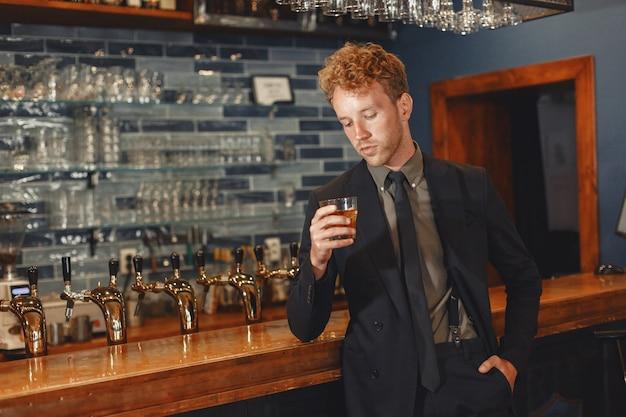 검은 양복을 입은 남자가 술을 마신다. 매력적인 남자는 유리에서 위스키를 ..