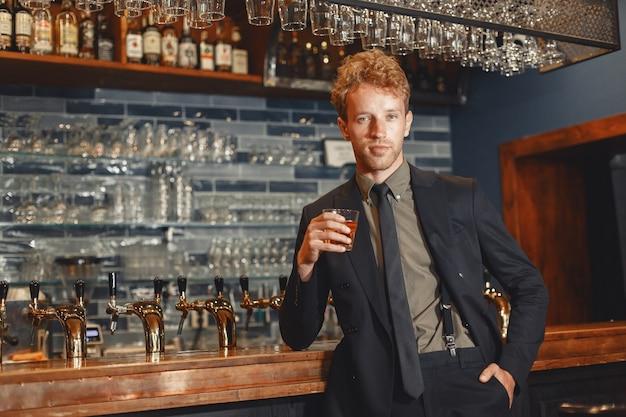 黒いスーツを着た男がアルコールを飲む。魅力的な男はグラスからウイスキーを飲みます。