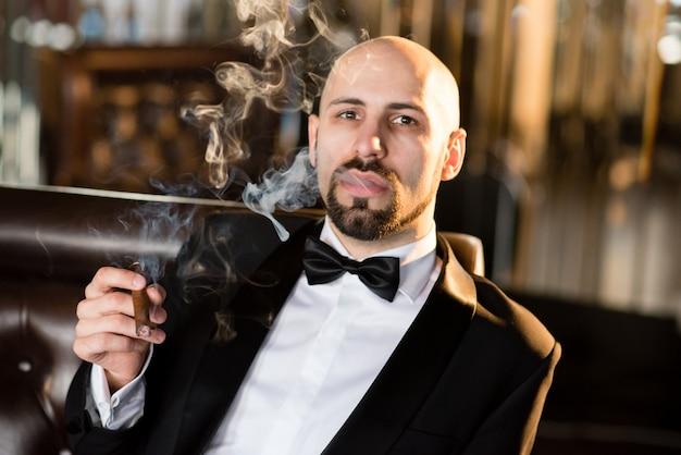 Мужчина в черном костюме курит сигару