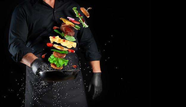 黒い制服を着た男が、チーズバーガーの材料を浮揚させる鋳鉄製の丸いフライパンを持っています:ゴマパン、チーズ、トマト、タマネギ、カツレツ、コショウ、コピースペース