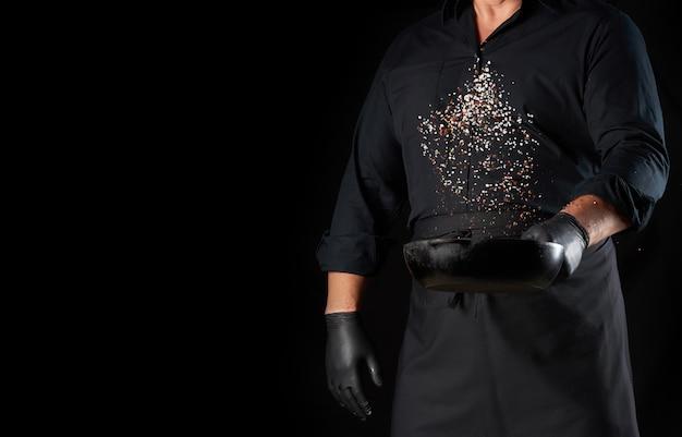 塩とコショウで丸い鋳鉄鍋を保持している黒い制服を着た男、シェフが黒の上にスパイスをトス