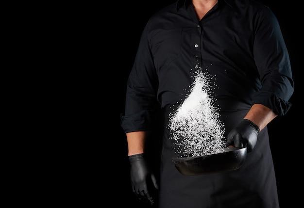 Мужчина в черной форме держит круглую чугунную сковороду с солью, повар подбрасывает белую соль
