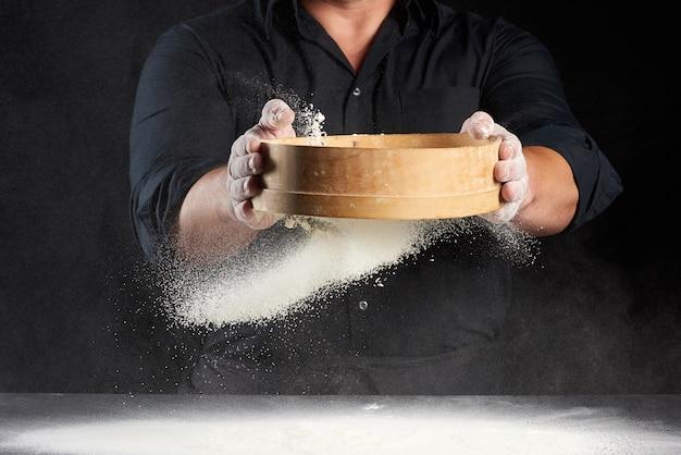 黒い制服を着た男が手に丸い木製のふるいを持ち、黒い小麦粉をふるいにかけます¡