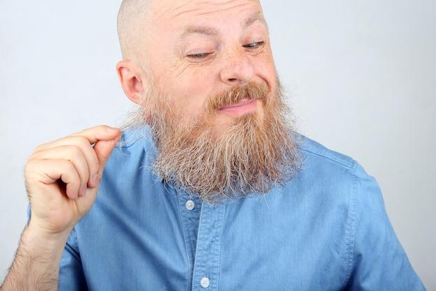 블루 데님 셔츠를 입은 남자가 수염을 건드린다.