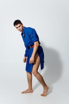 明るい背景のゲイモデルの青いドレスの男
