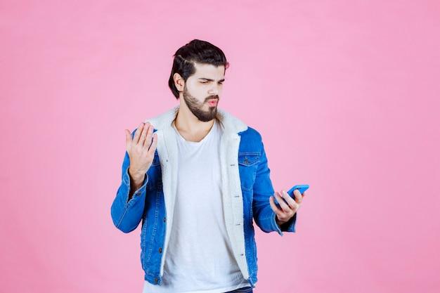 놀라움과 함께 자신의 휴대 전화를 찾고 파란색 재킷을 입은 남자.