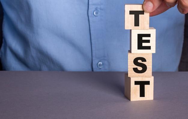 파란색 셔츠를 입은 남자는 수직으로 나무 큐브에서 테스트라는 단어를 구성합니다.