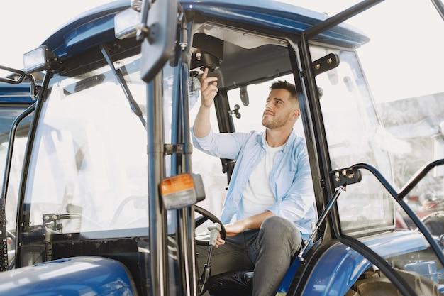 Мужчина в голубой рубашке. парень в тракторе. сельскохозяйственная техника.