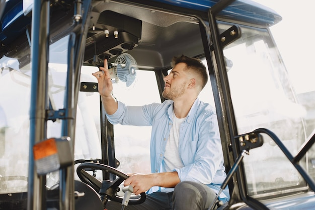파란색 셔츠에 남자입니다. 트랙터에있는 남자. 농업 기계.