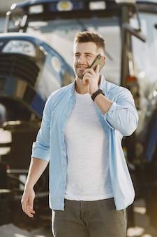 青いシャツを着た男。トラクターの男。農業機械。