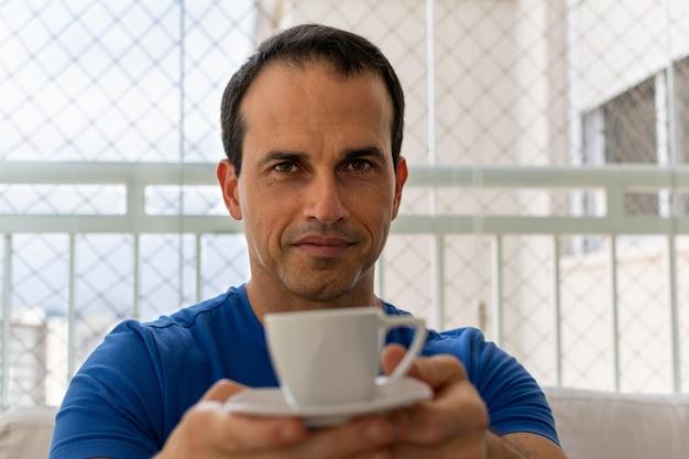 Мужчина в синей рубашке выпивает чашку кофе
