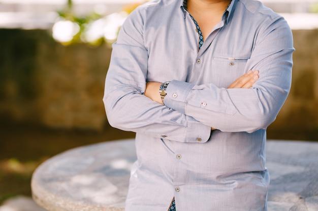 腕を胸に組んで青いシャツを着た男が石のテーブルに寄りかかる