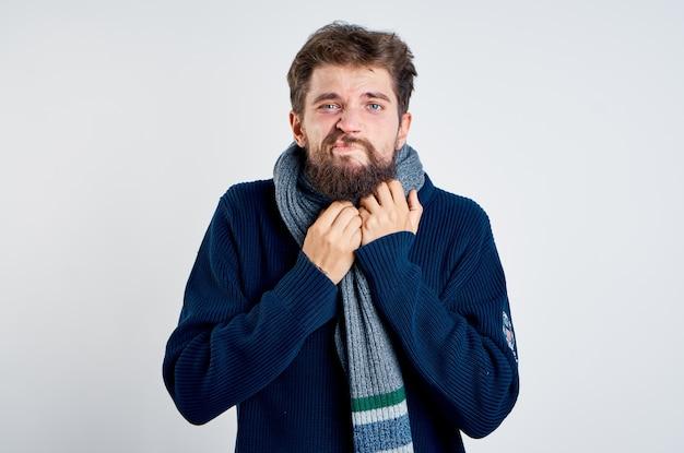 Мужчина в синем свитере с шарфом на шее крупным планом портрет обрезанный вид теплой одежды
