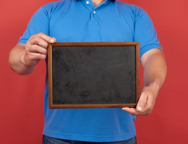 青いtシャツの男は、テキストを書き込むための空の長方形の木製フレームを保持しています。
