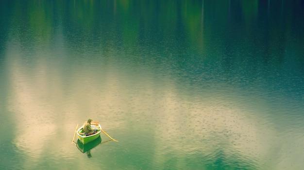 낮 동안 호수에 보트에 남자